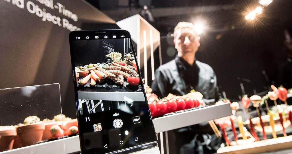 A Huawei phone being used at a public cooking demonstration